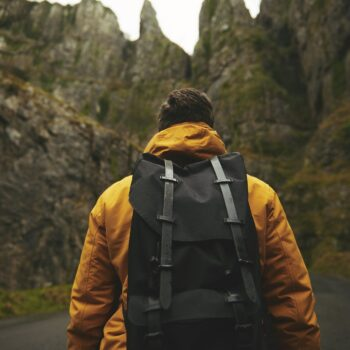 Man in Yellow Jacket with Black Backpack looking up at mountains